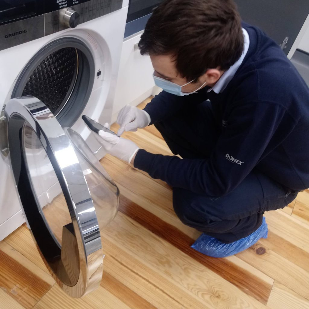Domex engineer inspecting washing machine in PPE COVID-19 safety precautions
