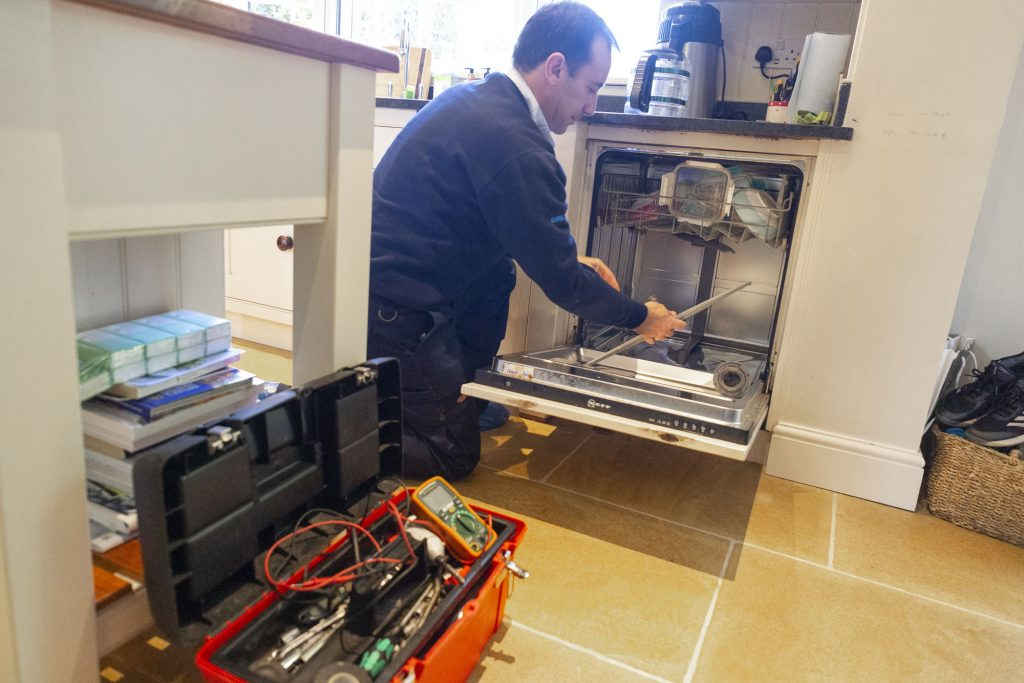 Domex engineer repairing dishwasher in Ilford