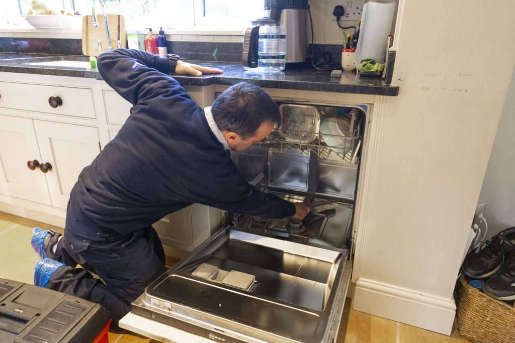 Domex engineer repairing dishwasher in Beckenham