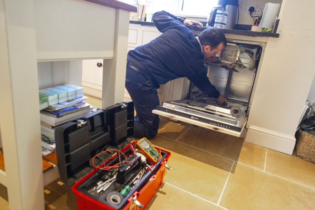 Domex engineer repairing dishwasher in Bromley